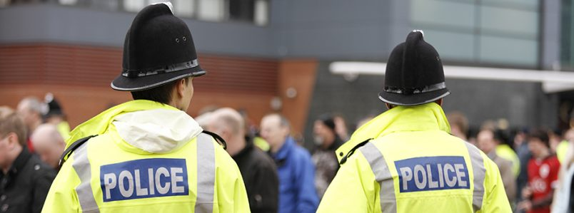 Two British policemen stand with backs to camera. Selectively focussed. A crowd of people appears in the background, out of focus. Policemen are wearing tall traditional British helmets and fluorescent Jackets.